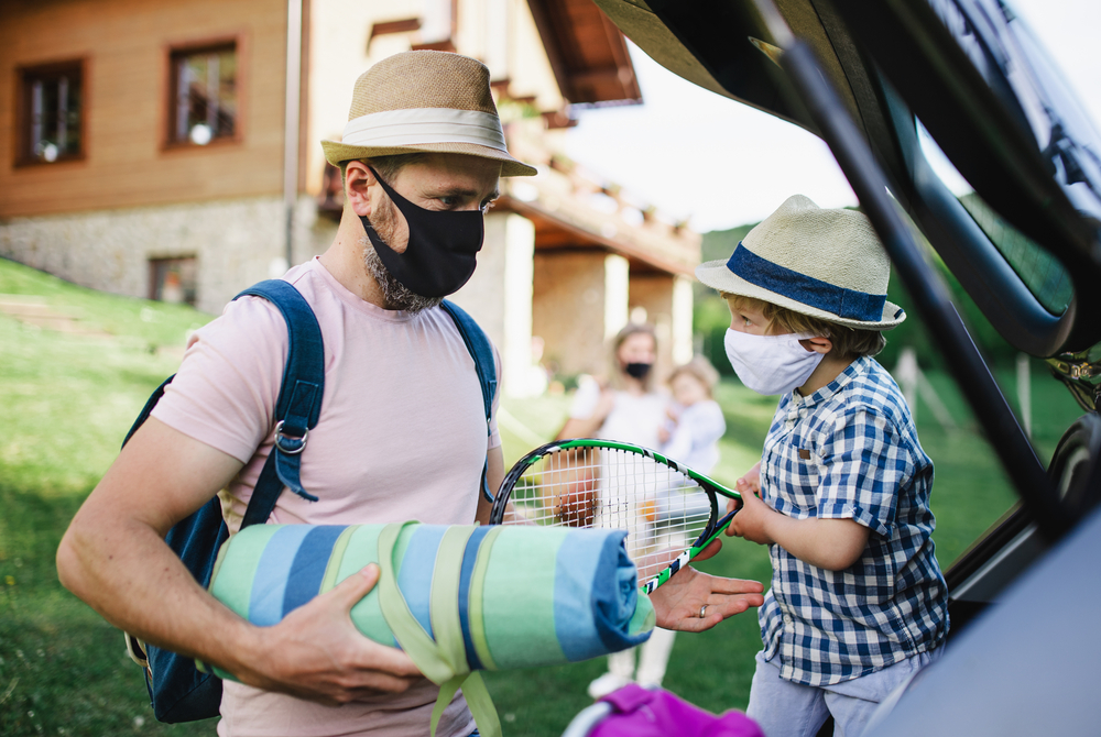 Happy family with two small children loading car for trip in countryside, wearing face masks.