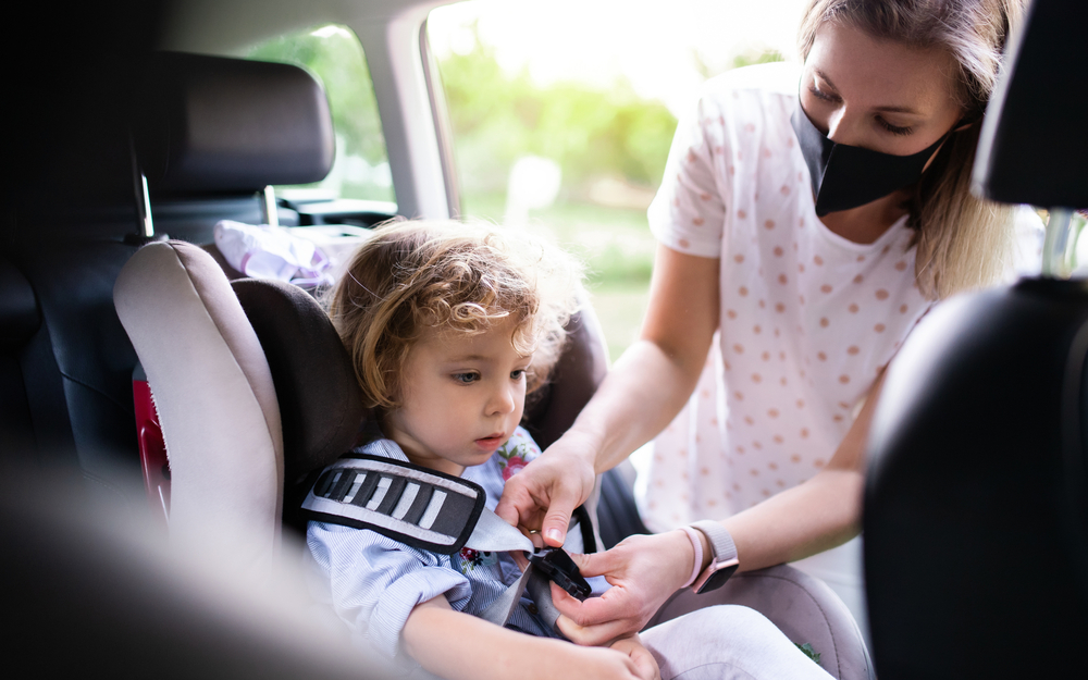 Mother putting small toddler daughter in car seat before trip, wearing face masks.