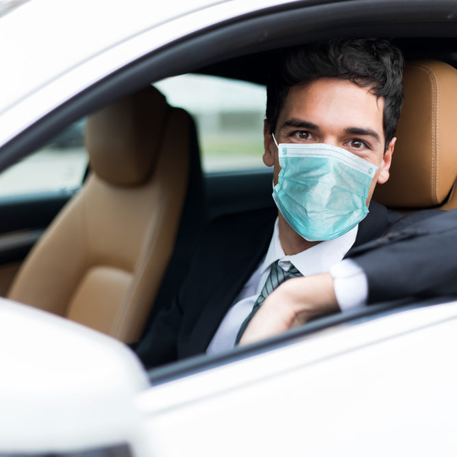 Handsome man driving his car wearing a mask, coronavirus concept